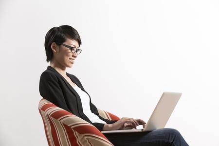 mujer china: Retrato de una mujer china feliz sentado en una silla con ordenador port�til Foto de archivo