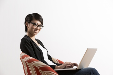 Portrait of a happy Chinese woman sitting on a chair using laptop