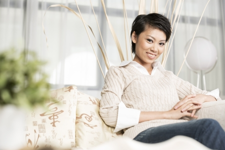 one mid adult woman only: Pretty Chinese woman relaxing at home on the sofa. Stock Photo