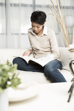 pleasure of reading: Chinese Woman reading a magazine while sitting on a sofa in her living room