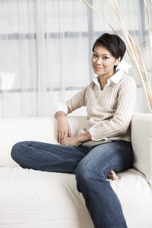 Pretty Chinese woman relaxing at home on the sofa. Stock Photo