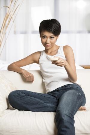 mujer china: Bastante joven mujer china con un mando a distancia para navegar por los canales mientras est� sentado en el sof�.