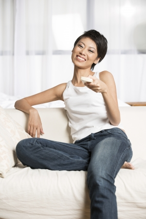 Pretty young Chinese woman using a remote control to channel surf while sitting on the couch.   photo