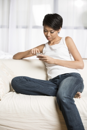 mujer china: Mujer bastante china que usa su tel�fono celular en casa en el sof�. Foto de archivo