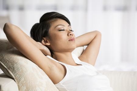 mujer china: Mujer china hermosa que duerme en el sof� en la sala de estar Foto de archivo