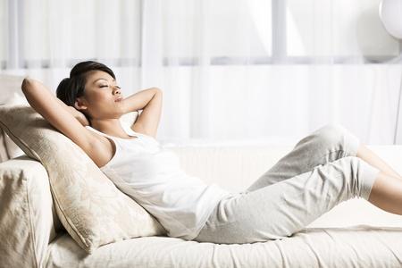 mujer china: Mujer china hermosa que duerme en el sof? en la sala de estar