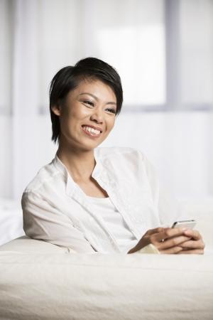 mujer china: Mujer bastante china que usa su tel?no celular en casa en el sof?