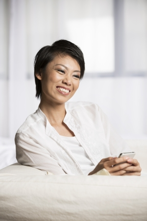 Pretty Chinese woman using her cell phone at home on the sofa. photo