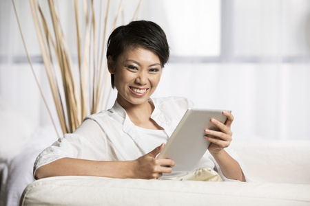 Portrait of a happy Chinese woman sitting on sofa using Digital Tablet photo