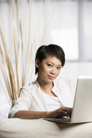 Portrait of a happy Chinese woman sitting on sofa using laptop photo