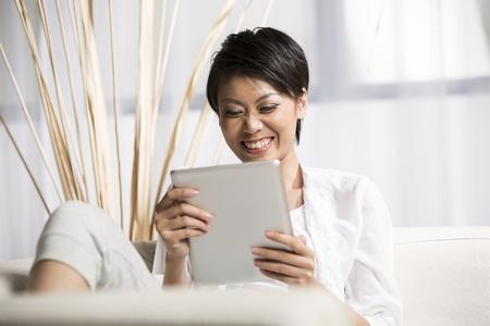 mujer china: Retrato de una mujer china feliz sentado en el sof? con la tableta digital Foto de archivo