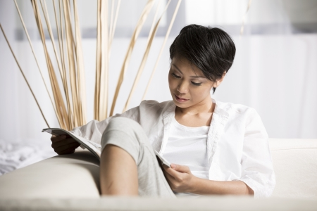 Chinese Woman reading a magazine while sitting on a sofa in her living room photo