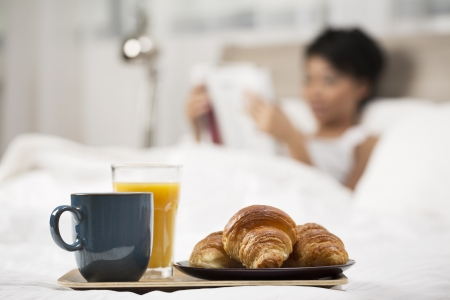 bed and breakfast: Pretty Chinese Woman having breakfast in bed Stock Photo
