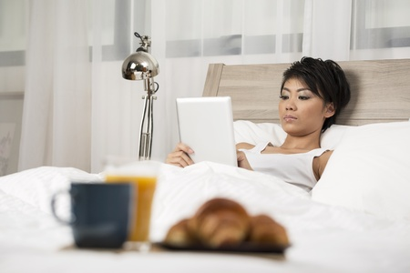Chinese Woman having breakfast in bed and reading her Digital Tablet photo