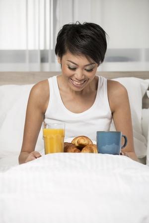 mujer china: Mujer bastante china de desayunar en la cama