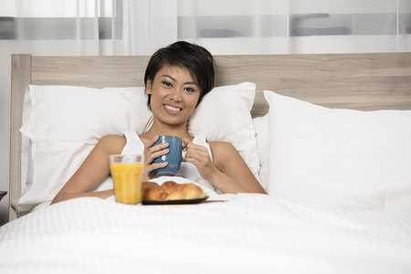Pretty Chinese Woman having breakfast in bed photo