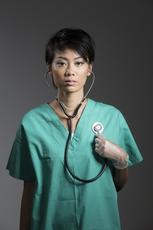 Chinese Female Doctor in surgical scrubs holding stethoscope to chest photo