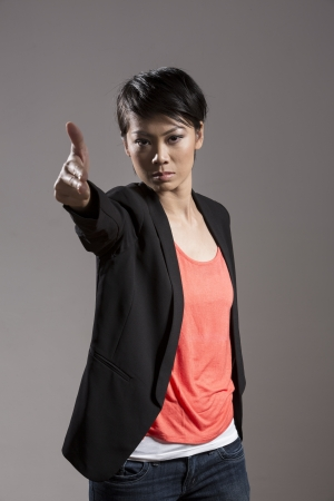 women with guns: Aggressive Asian woman pointing an imaginary gun