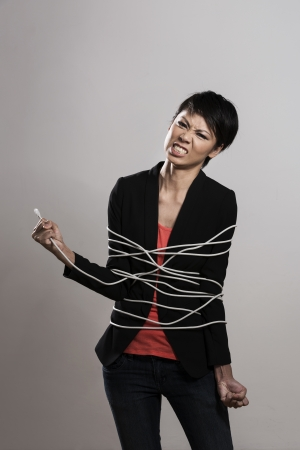 hair wrapped up: Chinese woman trangled up in computer network cable. Conceptual image. Stock Photo