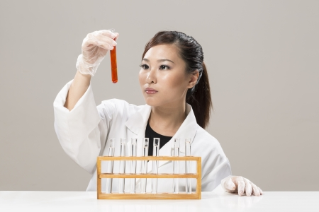 Female Chinese Healthcare professional or scientific researcher looking at a row of test tubes Stock Photo - 19803768