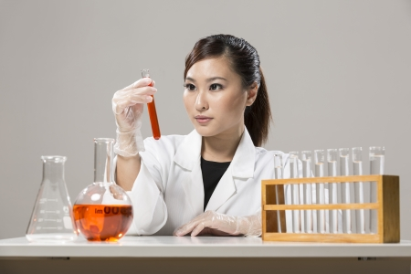 Female Chinese Healthcare professional or scientific researcher looking at a row of test tubes Stock Photo - 19803727