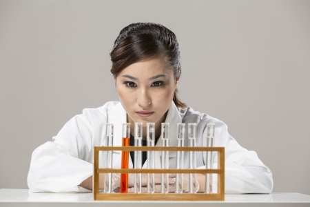 Female Chinese Healthcare professional or scientific researcher looking at a row of test tubes Stock Photo - 19803728