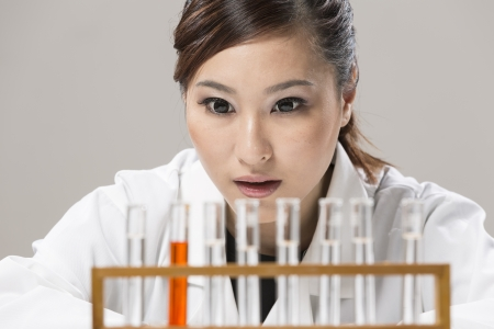 Female Chinese Healthcare professional or scientific researcher looking at a row of test tubes Stock Photo - 19803685
