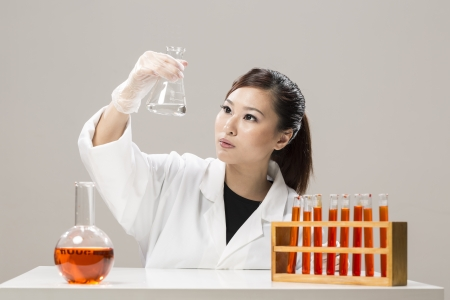 Female Chinese Healthcare professional or scientific researcher looking at a row of test tubes photo