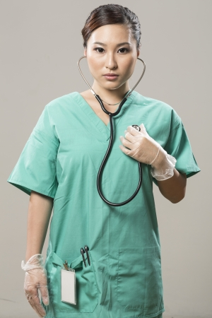 surgical scrubs: Chinese Female Doctor in surgical scrubs holding stethoscope to chest Stock Photo
