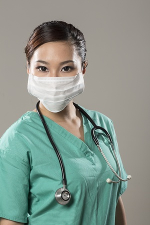 surgical light: Chinese doctor wearing a face mask, green scrubs and stethoscope.