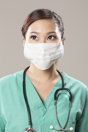 Chinese doctor wearing a face mask, green scrubs and stethoscope photo