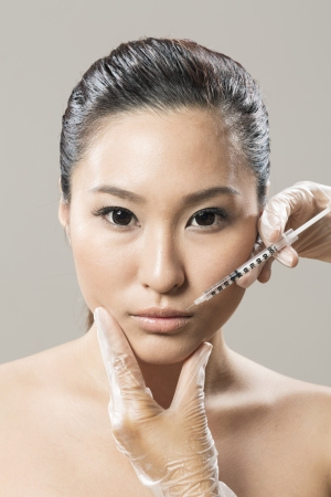 Chinese woman receiving a botox injection. Beauty Treatment. photo