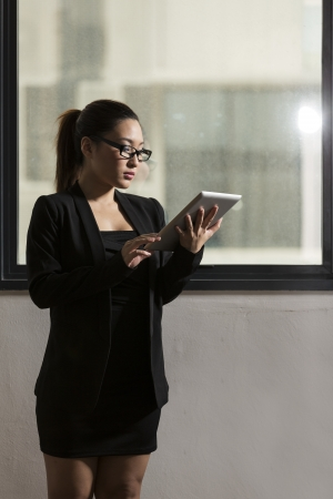 Attractive young Chinese businesswoman reading a tablet computer photo