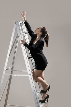 Chinese businesswoman wearing a dark suit and climbing a ladder photo