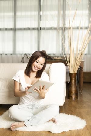 mujer china: Retrato de una mujer china feliz sentado en el sof?on la tableta digital