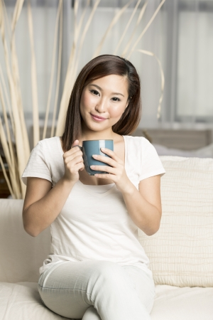 Beautiful chinese woman holding a coffee cup while sitting on her sofa photo