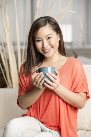 mujer china: Hermosa mujer china sostiene una taza de caf?ientras estaba sentado en su sof?