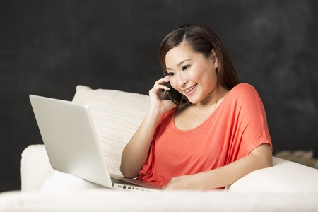 computer model: Portrait of a happy Chinese woman sitting on sofa using laptop and talking on mobile phone.