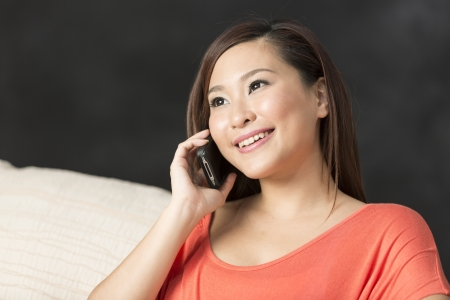 Pretty Chinese woman talking on mobile phone at home on the sofa. photo