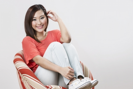 Portrait of a beautiful Chinese woman posing with a chair. photo