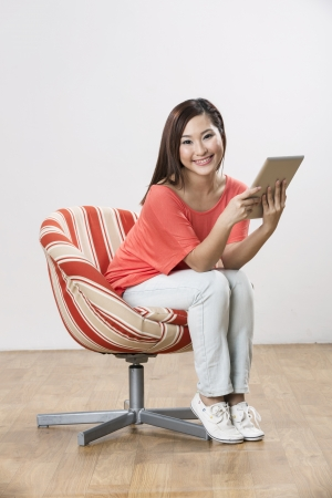 Portrait of a happy Chinese woman sitting on a chair using Digital Tablet photo