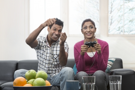Indian couple, man and woman, having fun playing video console games together. Stock Photo - 19871493