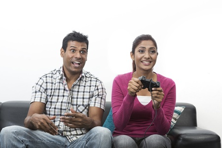 Indian couple, man and woman, having fun playing video console games together. Stock Photo - 19871403