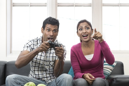 Indian couple, man and woman, having fun playing video console games together. photo