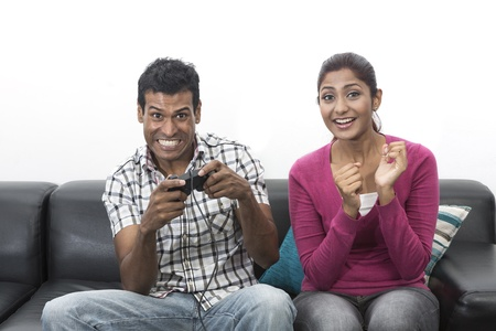 Indian couple, man and woman, having fun playing video console games together. Stock Photo - 19871388