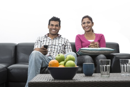 Happy Indian couple on the sofa watching tv in the living room Stock Photo - 19871474