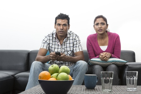 Happy Indian couple on the sofa watching tv in the living room Stock Photo - 19871406