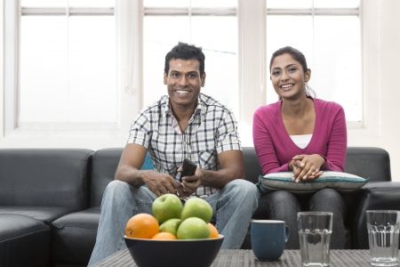 Happy Indian couple on the sofa watching tv in the living room Stock Photo - 19871404