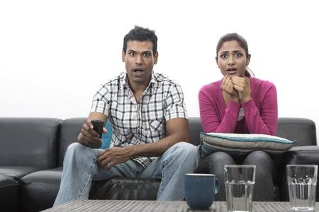 pareja viendo television: Feliz pareja de indios en el sof? viendo la televisi?n en la sala de estar