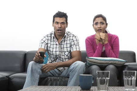 Happy Indian couple on the sofa watching tv in the living room Stock Photo - 19871381